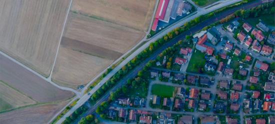 image vue du ciel avec des champs séparés d'une zone pavillonnaire par une route